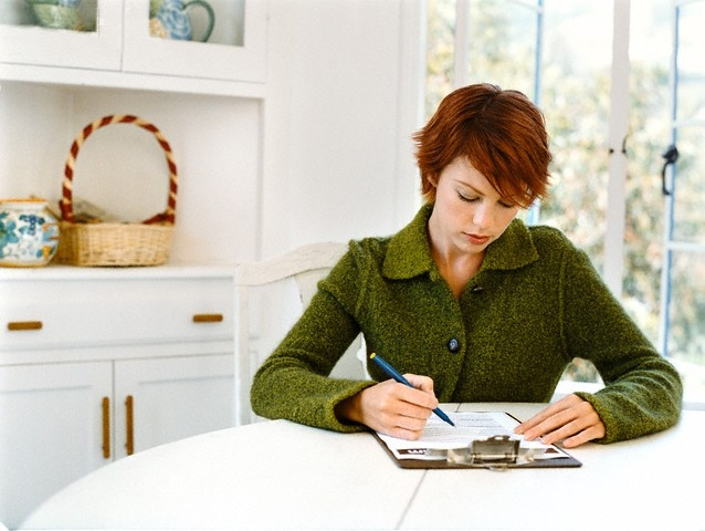 Woman Filling Out Form At Kitchen Table throughout Woman Filling Out Form 25120
